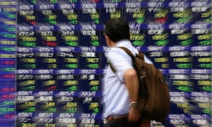 A man watches a monitor displaying the Tokyo stock index.