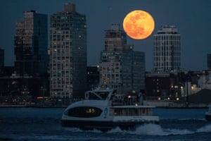 New York, US. A full worm supermoon rises over Williamsburg waterfront