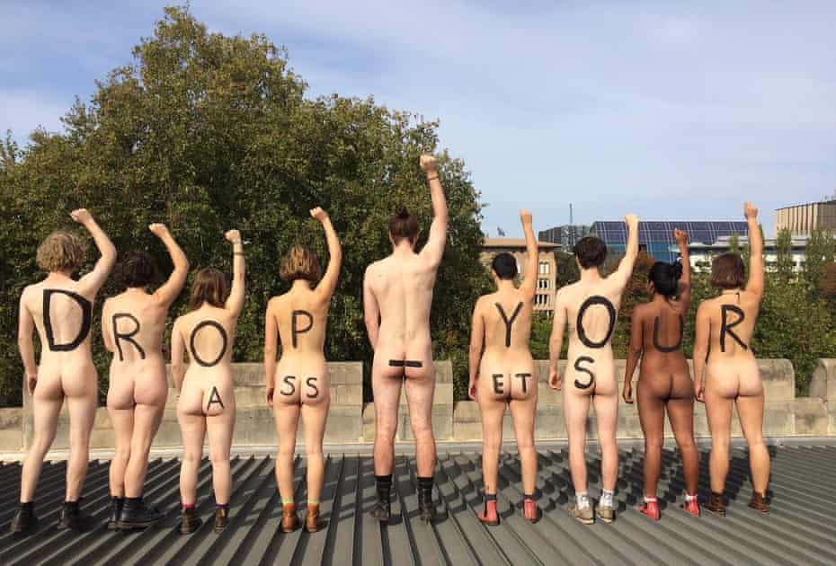 """Nine students from Melbourne University stood on the roof of the campus' Old Quad building and stripped off to reveal the message """"drop your assets"""" painted on their bare backs and bottoms. The group protested the university's investment in the fossil fuel industry."""