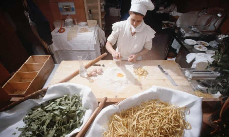 A female chef prepares pasta