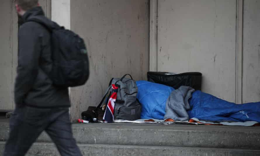 A homeless person sleeps on the streets