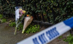 Bouquets of flowers lie at the scene of the fatal stabbing