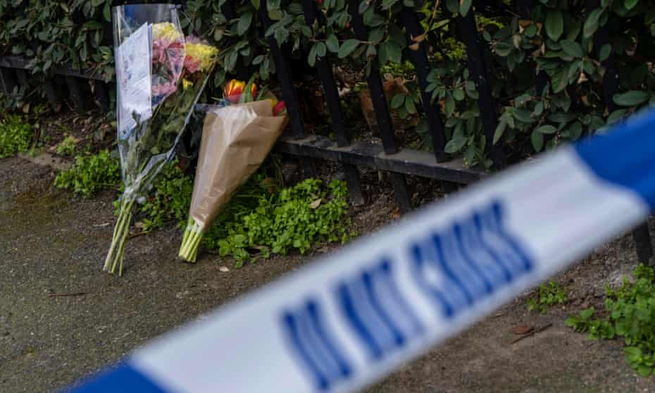 Bouquets of flowers lie at the scene of a fatal stabbing in London