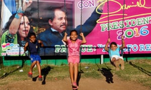 Children play in front of a campaign poster of Daniel Ortega and Rosario Murillo in Managua, Nicaragua