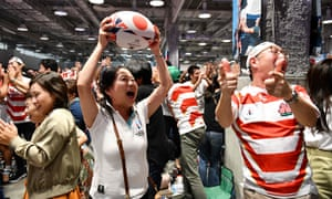 Fans watching from Tokyo celebrate after Japan score a try against Scotland.
