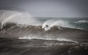 A surfer rides a large wave off Sydney's Fishermans beach during a stormy day