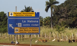 Goat herders sit on rail tracks as their animals graze, near a street sign indicating directions to downtown Havana and the José Martí international airport in Cuba.
