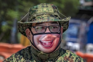 Brace yourself: a policeman wears a dental-themed face mask at a quarantine checkpoint in Marikina, Philippines