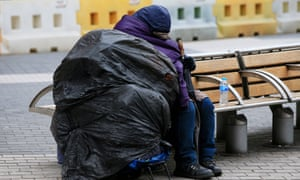 A homeless person sleeps on a bench on a London street<br>