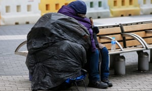 A homeless person on a bench.