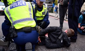 A man is detained by police in Victoria, central London