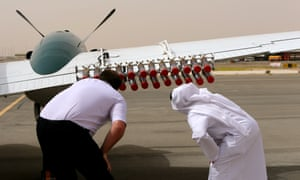 A pilot and a United Arab Emirates official check salt flares on a plane. They will be fired into a cloud to increase condensation and in the hope of triggering rainfall.