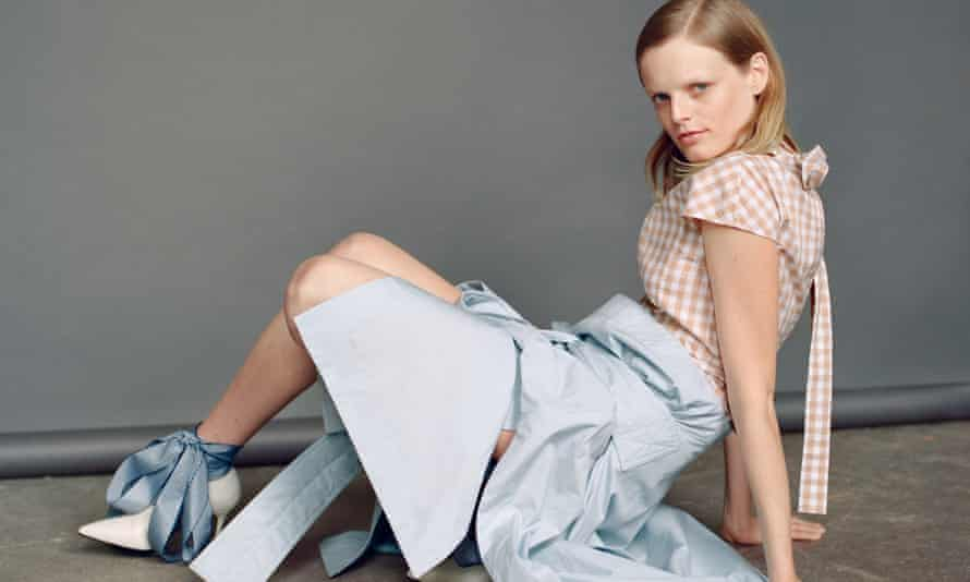 Hanne Gaby Odiele sitting on the floor in a pale blue puffy skirt, checked top, white high heels and with a big blue bow around her ankle