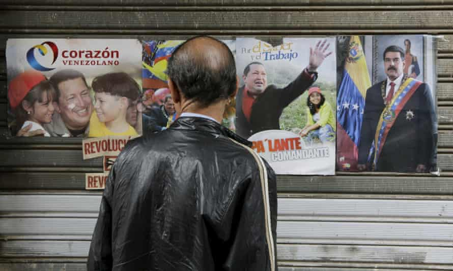 A man looks at posters of Venezuela's late President Chavez (left and centre) and its current president, Nicolás Maduro.