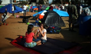 Migrants, part of a caravan of thousands from Central America trying to reach the United States, play together as they rest in a temporary shelter in Tijuana, Mexico.