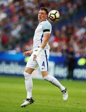 Phil Jones of England heads the ball.