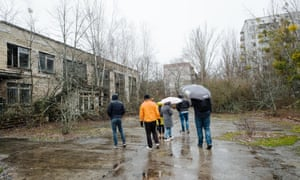 Tourists wander about the abandoned city of Pripyat.