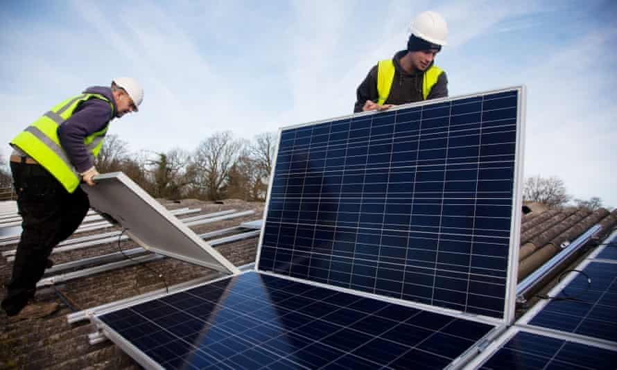 Andy Tyrrell and Jake Beautyman installing solar panels on a barn roof at Grange Farm, near Balcombe, a village which was at the centre of protests against fracking.