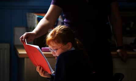 A teaching assistant helps a child to read
