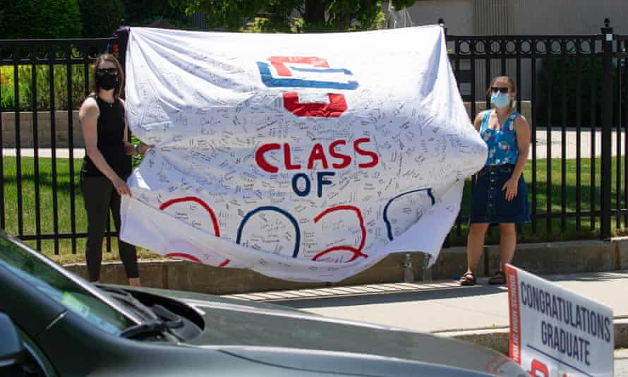 Teachers stand with a large banner with the names of the graduating seniors of the class of 2020 while cars carrying the graduates drive past outside Central Catholic high school in Lawrence, Massachusetts.