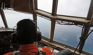 A crew of an Indonesian Air Force C-130 airplane of the 31st Air Squadron scans the horizon during a search operation for the missing AirAsia flight 8501 jetliner over the waters of Karimata Strait in Indonesia.