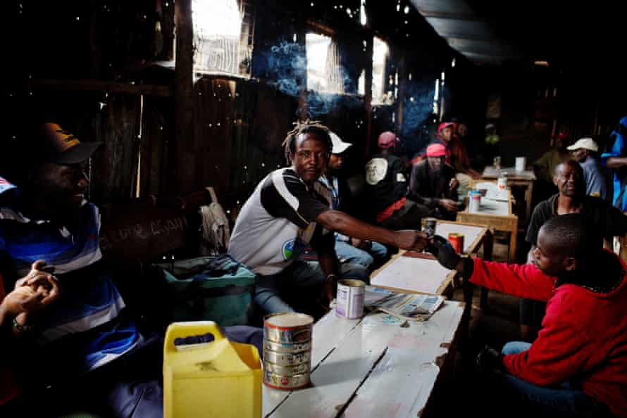 Men drink changaa – home-brewed alcohol – in a bar in Kibera