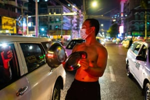 A resident beats metal utensils during a noisy protest in Yangon