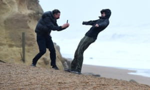 Walkers enjoy leaning into the wind in West Bay, Dorset, on Sunday as Storm Ciara swept the UK