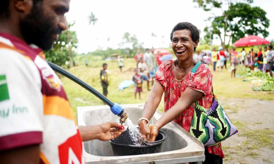 A woman washes her hands at the running water station which was set up as a requirement to keep the Gunanur market running in accordance with state of emergency measures cross East New Britain province, Papua New Guinea.