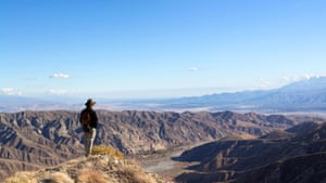 Man stands on top of a peak looking at Sand to Snow national monument, California, USA.