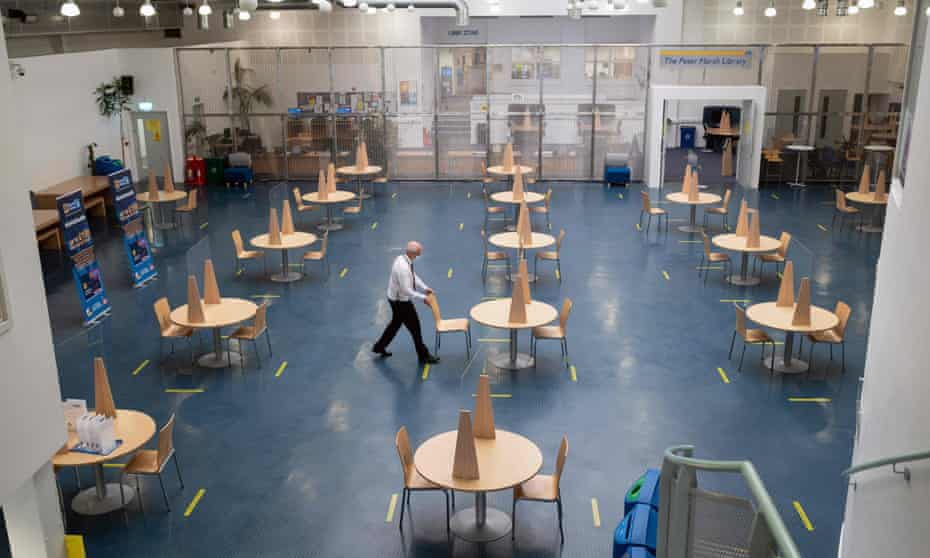 A member of staff at the University of Bolton inspects a communal workspace with socially distanced seating and perspex screens before students return next week.