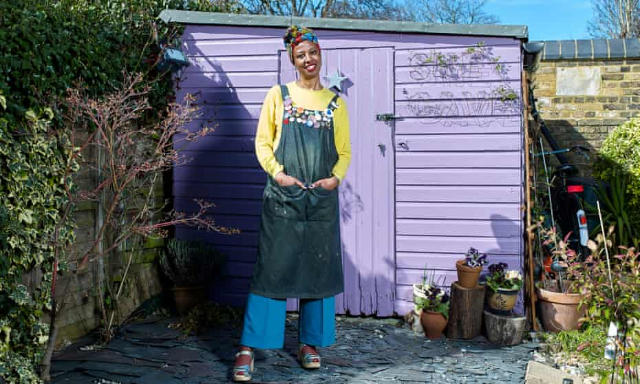 Angela Benjamin standing outside her lilac painted workshop shed in Ealing, London.