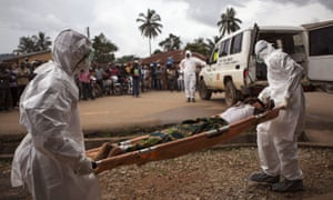 Healthcare workers carry a suspected Ebola sufferer to an ambulance in Kenema