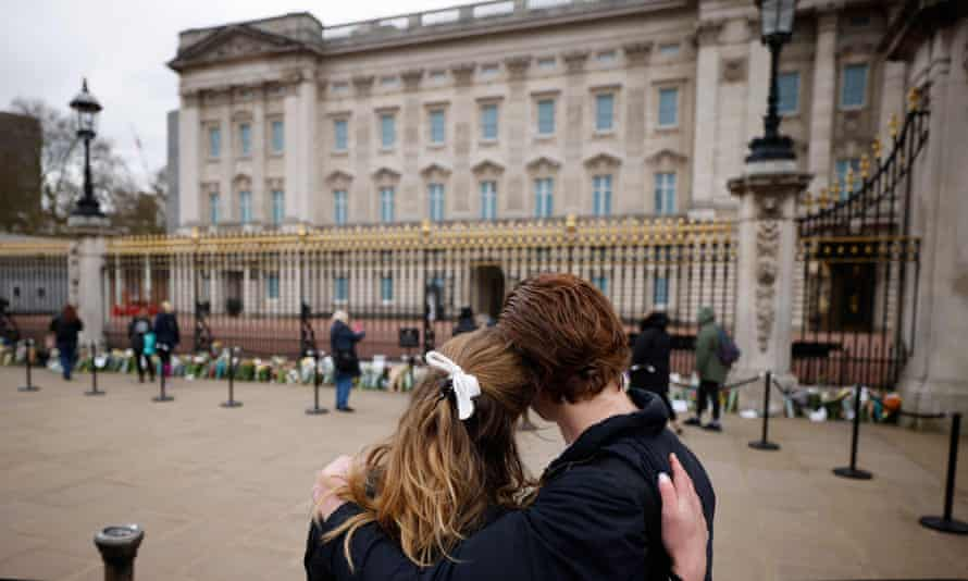 A couple watches as supporters leave floral tributes to Britain's Prince Philip.