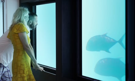 Visitors staring at fish in a Reefsuites suite.