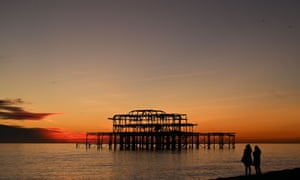 The sun sets beyond the timber remains of the West Pier at Brighton beach