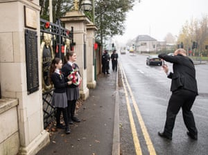 Two schoolgirls and their father prepare to lay a homemade wreath ready to lay at the memorial garden in Abebargoed