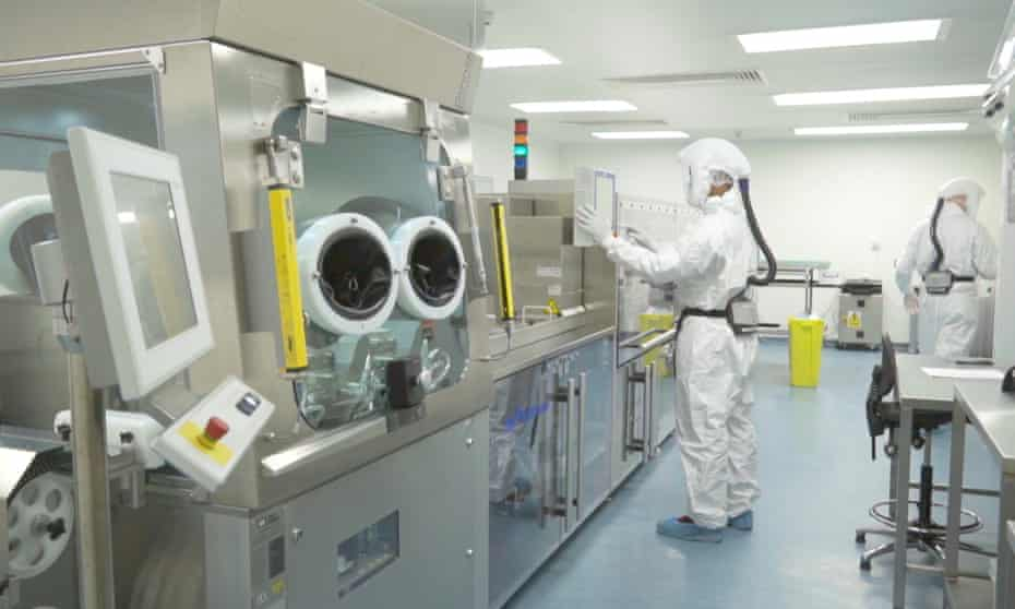 Two people in a lab wearing protective clothing