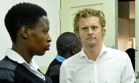 Jack Marrian is guarded by a police officer in court in Nairobi.