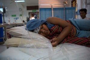 Chan Pheakdey lies in bed at Angkor hospital