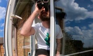 David Nunn straddles his windowsill to get some sun