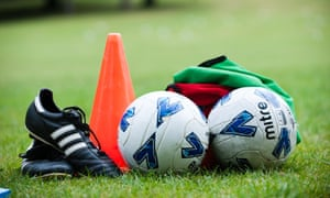 Football boots, a red cone, two footballs and green and red tops on the grass waiting for a holiday football coaching course