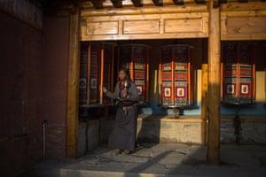 An Ethnic Tibetan pilgrim turns prayer-wheels near the Labrang Monastery in Xiahe, an ethnically-Tibetan town in Gansu province, China