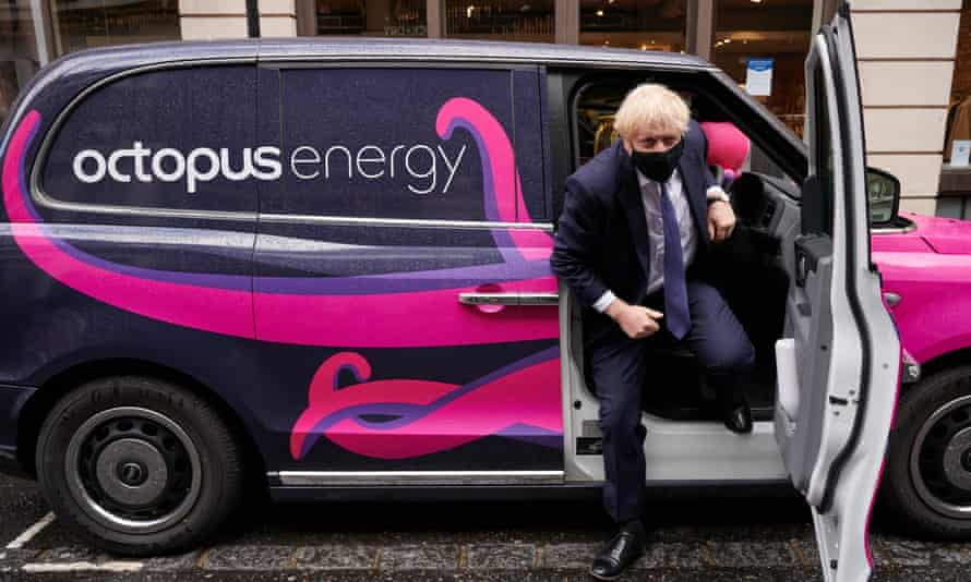 Boris Johnson gets out of a branded electric taxi on a visit to the headquarters of Octopus Energy on October