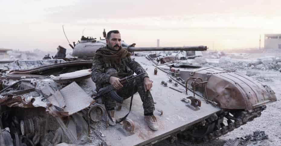 Agid, a YPG fighter, sits atop a destroyed Isis tank in Kobane.