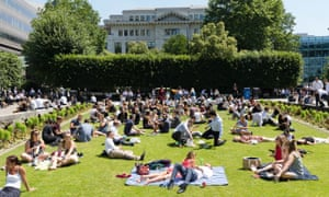 People enjoying the hot and sunny weather at lunchtime near St Paul's Cathedral in London.