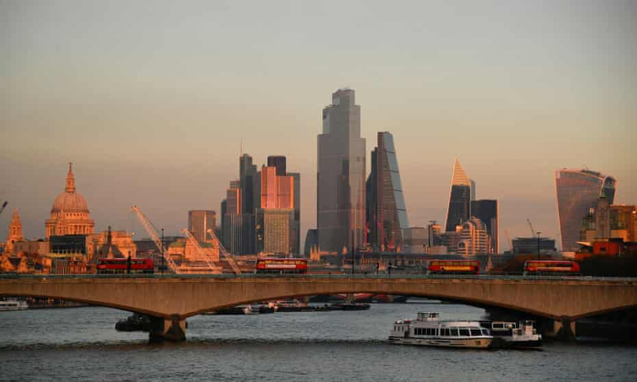 St. Paul's Cathedral and buildings of the City of London financial district are seen as buses cross Waterloo bridge at sunset