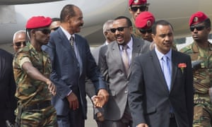 Isaias, centre left, and Ethiopia's president, Abiy Ahmed, centre, greet each other at the airport.