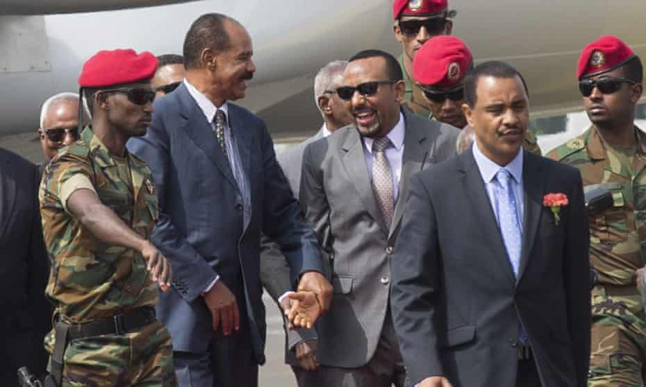 Isaias Afwerki, centre left, and Ethiopia's prime minister, Abiy Ahmed, centre, greet each other at the airport.