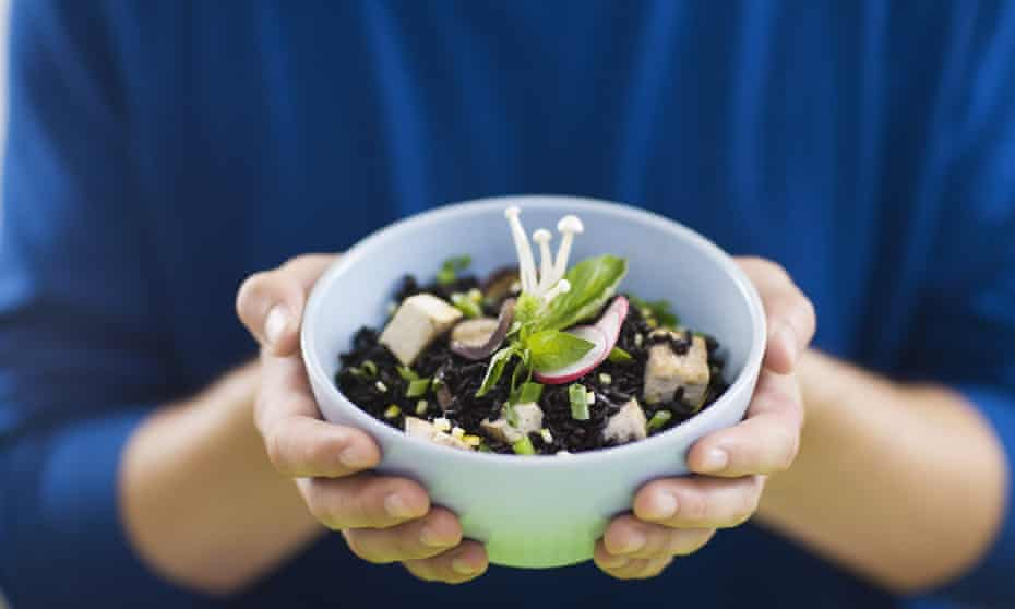 A close-up of a white bowl containing a dish of black rice, tofu, and enoki mushroom salad being held by a person wearing a blue jumper.